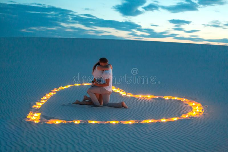 Couple in love romantic hugs in sand desert. Evening, romantic atmosphere, in sand burn candles in form of heart.  stock photo