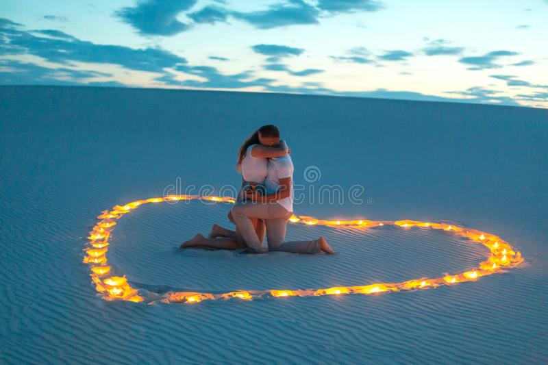 Couple in love romantic hugs in sand desert. Evening, romantic atmosphere, in sand burn candles in form of heart.  stock photos