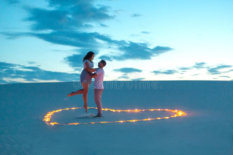 Couple in love romantic hugs in sand desert. Evening, romantic atmosphere, in sand burn candles in form of heart.  stock image
