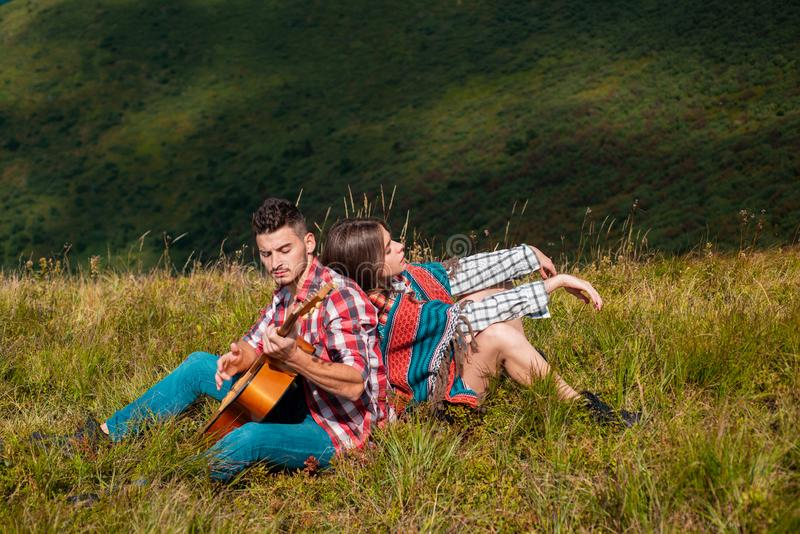 Couple in love. Romantic trip to the nature. Happy couple travelling in mountains and playing guitar. royalty free stock photo