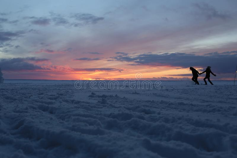 Couple love running snow covered ice lake silhouette stock image