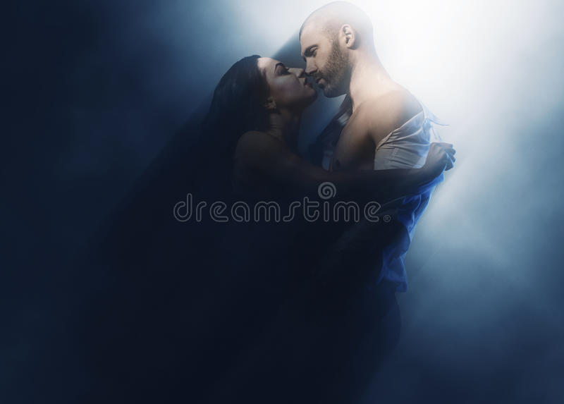 Couple in love. Sensual brunette and handsome men kissing. Image with a blurry effect royalty free stock image