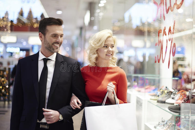 Couple in love during the shopping. Shopping adult couple looking for sales royalty free stock photography