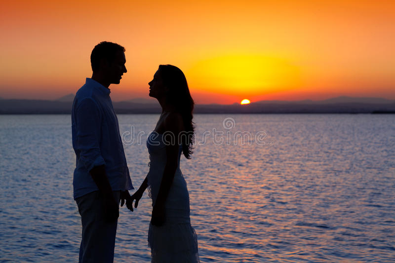 Couple in love silhouette at lake sunset. Couple in love back light silhouette at lake orange sunset stock image