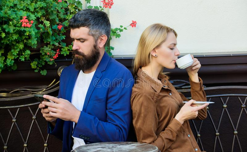 Couple in love sit cafe terrace enjoy coffee. Man secret messaging cheating on wife. Cheat and betrayal. Family weekend. Married lovely couple relaxing royalty free stock image