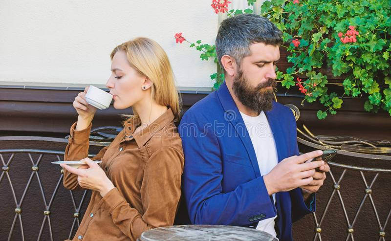 Couple in love sit cafe terrace enjoy coffee. Man secret messaging cheating on wife. Cheat and betrayal. Family weekend. Married lovely couple relaxing stock image