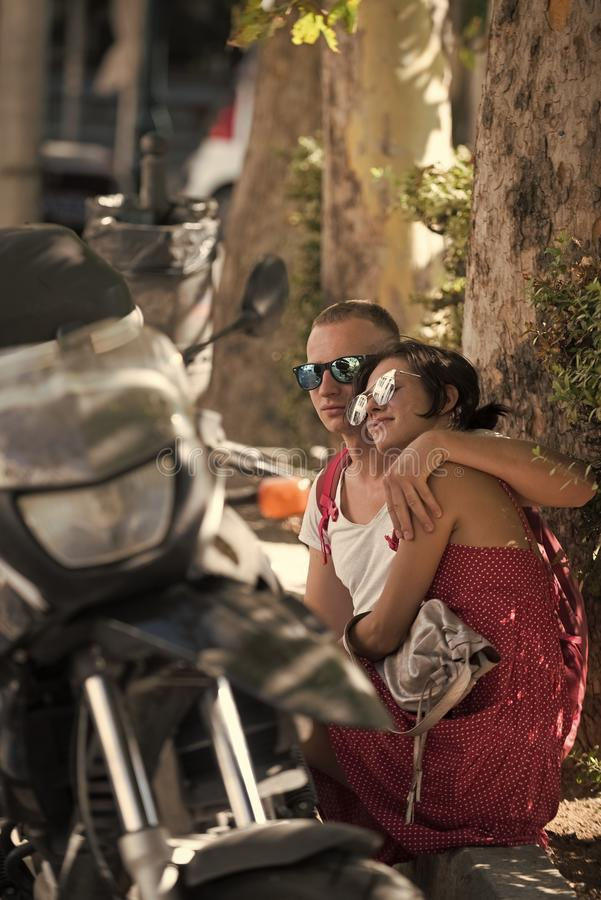 Couple in love sit in shadow of trees on hot summer day near parked motorbike, defocused. Refreshment concept. Couple royalty free stock photo