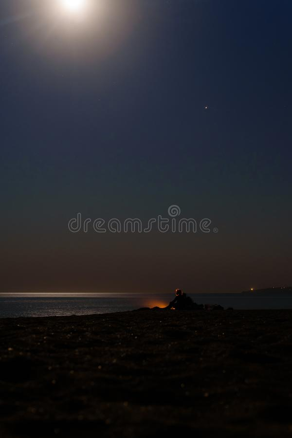 Romance by the fire by the sea. Couple in love sitting on the beach in front of a fire stock photo