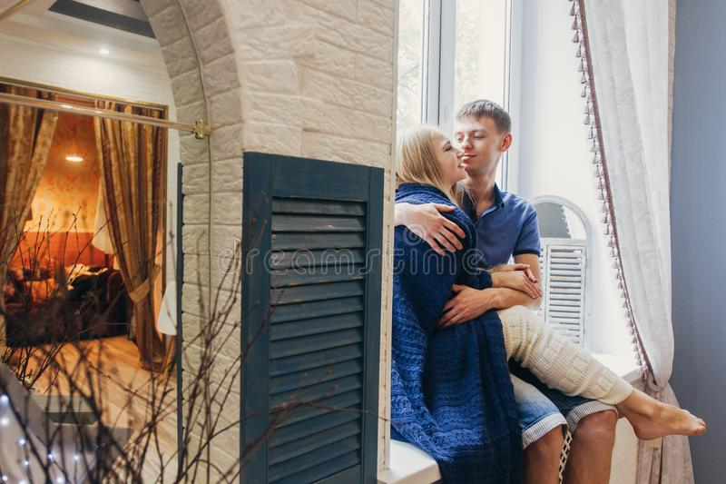 Couple in love sitting at home on the window. Tender loving embrace of newlyweds. Fun morning happy mood of a loving couple. Girl. Cuddles up to boyfriend royalty free stock photography