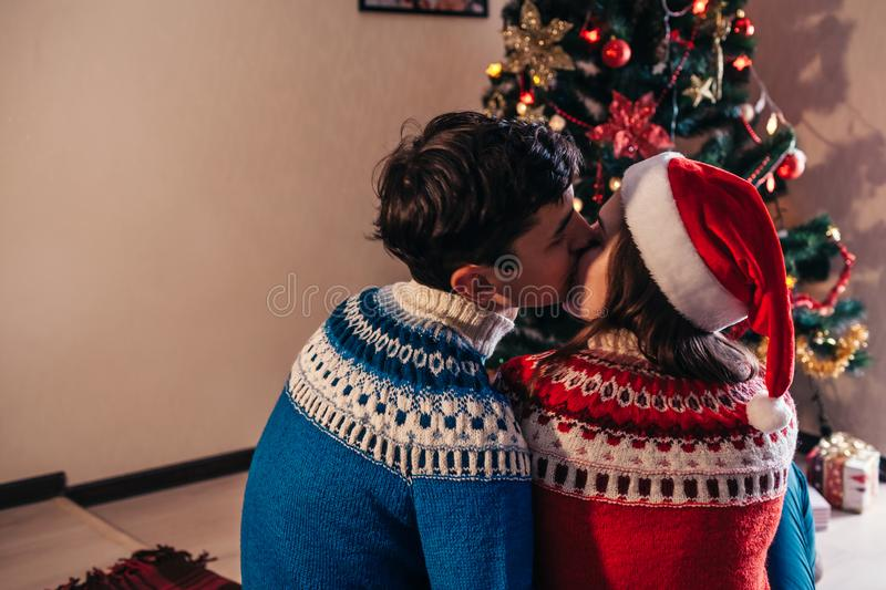 Couple in love sitting next to a Christmas tree, wearing Santa`s hat and hugging. Young people celebrating New year at home at royalty free stock images