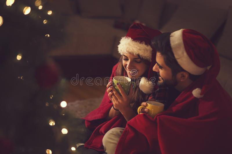 Joy of Christmas and love. Couple in love sitting next to a Christmas tree, wearing Santa`s hats, drinking hot tea and enjoying romantic moments together. Focus stock photos