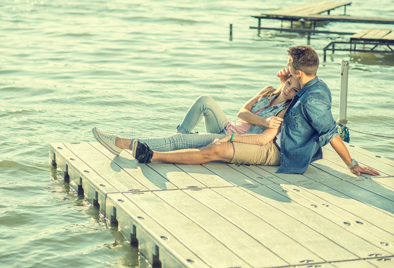 Couple in love sitting on the pier, embrace royalty free stock photo