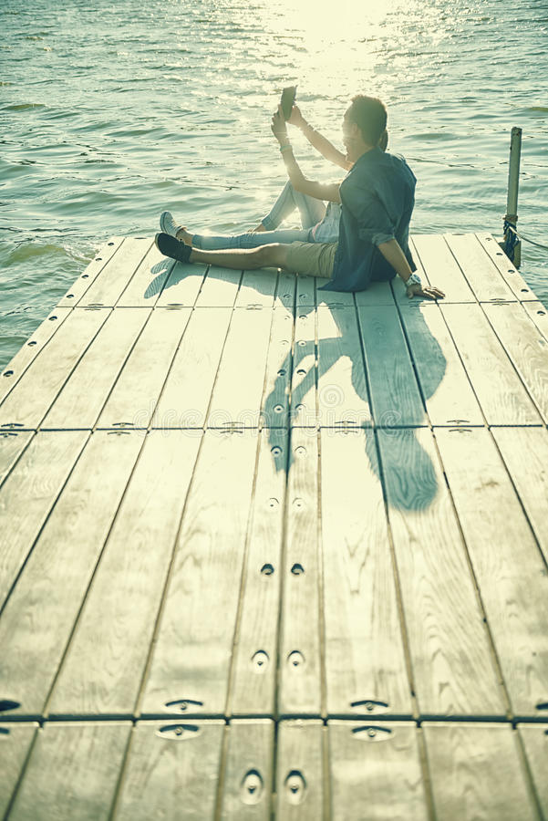 Couple in love sitting on the pier, selfie stock photo