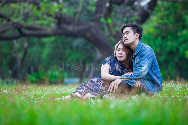 Couple in love sitting and relax on grass embracing each other in park romantic royalty free stock photo