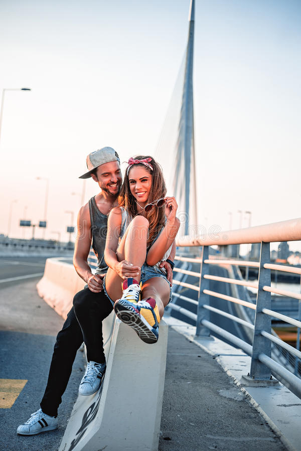 Couple in love sitting by the street royalty free stock image