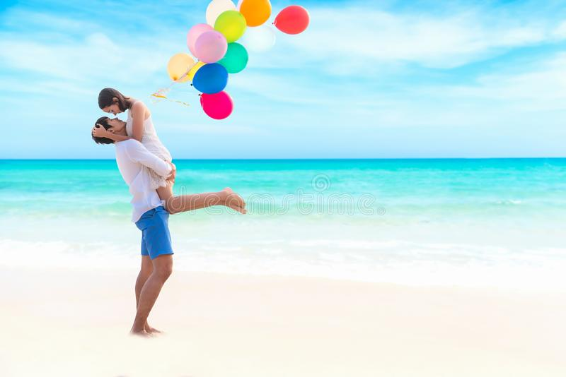 Couple in love. Smiling asian young man is holding girlfriend in his arms on the beach with multi color balloon, royalty free stock images