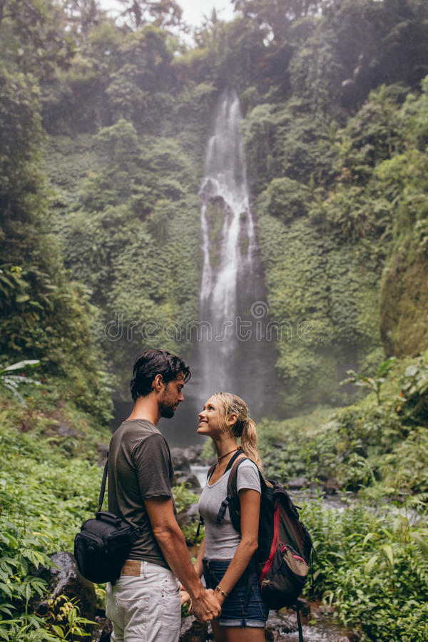 Couple in love standing near a waterfall in forest royalty free stock image