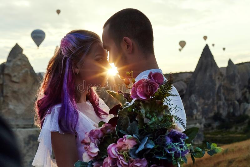 Couple in love stands on background of balloons in Cappadocia. Man and a woman on hill look at a large number of flying balloons. Couple in love stands on stock photos