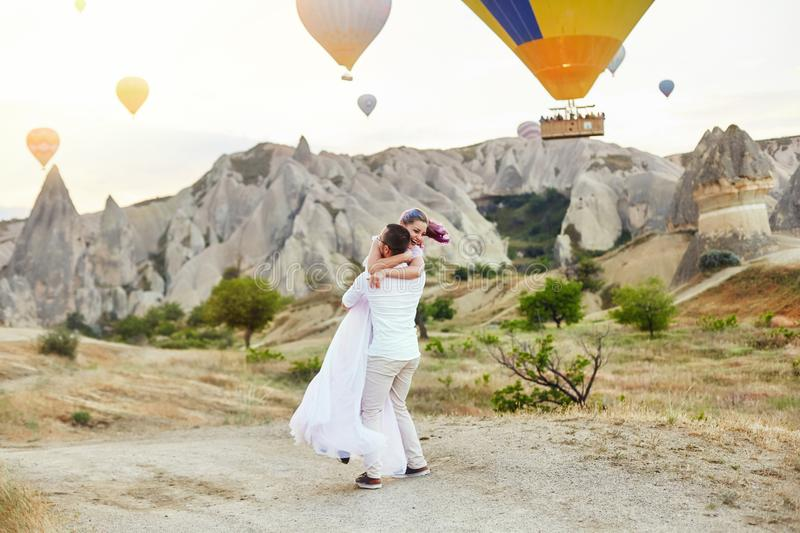 Couple in love stands on background of balloons in Cappadocia. Man and a woman on hill look at a large number of flying balloons. Couple in love stands on stock image