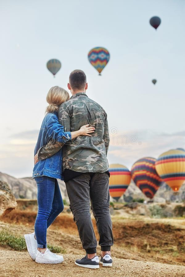 Couple in love stands on background of balloons in Cappadocia. Man and woman on hill look at a large number of flying balloons. Couple in love stands on royalty free stock images