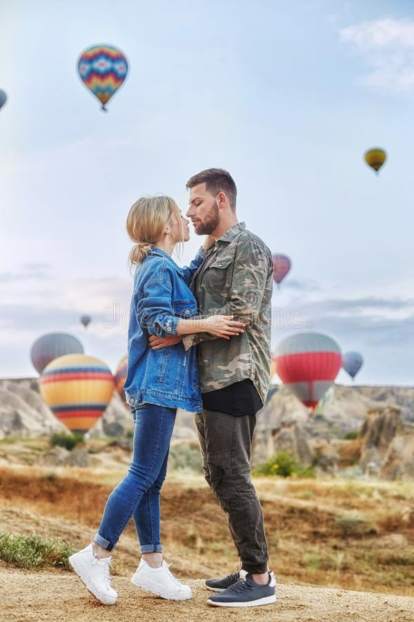 Couple in love stands on background of balloons in Cappadocia. Man and woman on hill look at a large number of flying balloons. Couple in love stands on royalty free stock photography