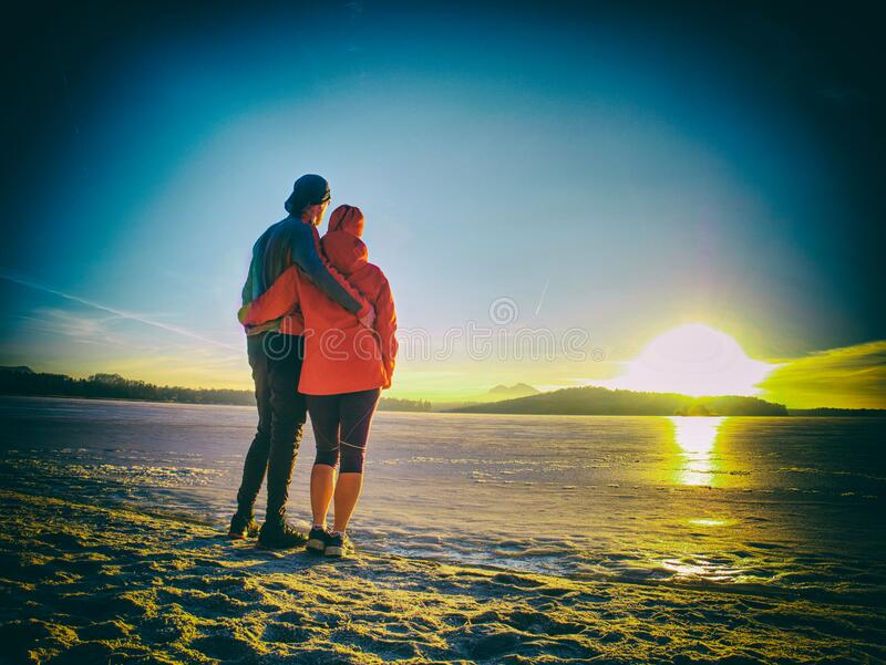 Couple in love stay at snow covered ice on the lake royalty free stock images