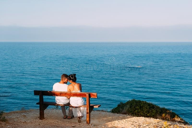 Couple in love at sunset. Man and woman at dawn. Couple in love at sunset. Man and women at dawn. Couple sitting on a bench by the sea. Couple kissing by the sea royalty free stock images