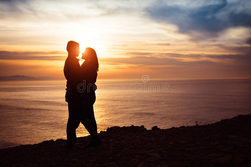 Couple in love at sunset. Young couple in love at sunset towards the sea. Lovers hugging in romantic scene royalty free stock photos