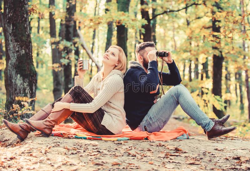 Couple in love tourists relaxing picnic blanket. Man with binoculars and woman with metal mug enjoy nature park. Park royalty free stock photos