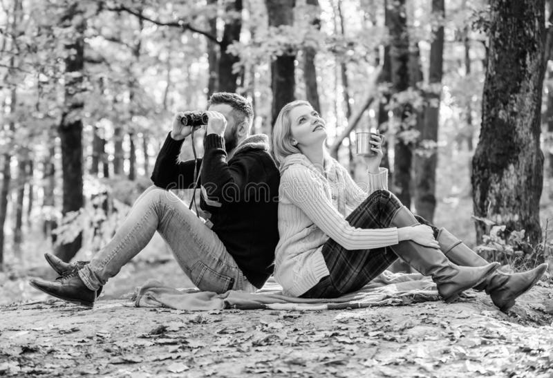 Couple in love tourists relaxing picnic blanket. Man with binoculars and woman with metal mug enjoy nature park. Park. Couple in love tourists relaxing picnic stock photos