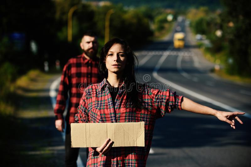 Couple in love travelling by hitchhiking, defocused. Couple in love travelling by hitchhiking, copy space. Woman try to stop car with blank cardboard sign and royalty free stock images