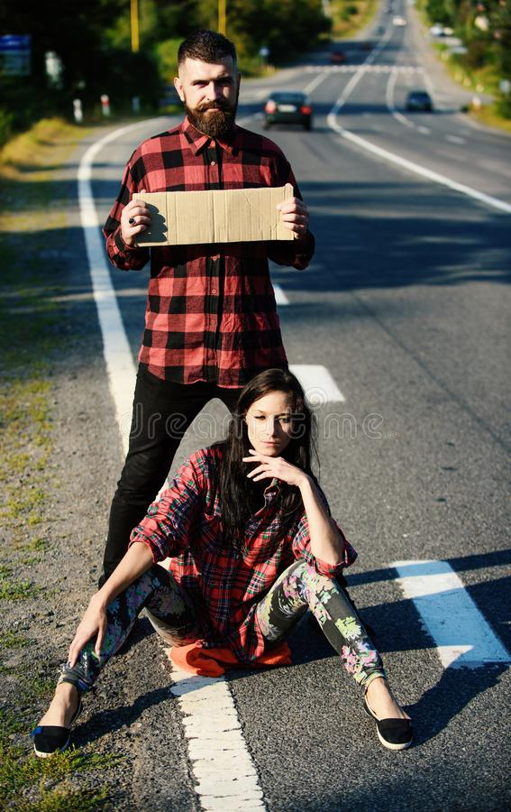 Couple in love travelling by hitchhiking, girl sit on road. Copy space. Man try to stop car with cardboard sign. Travelling and hitchhiking concept. Couple royalty free stock images
