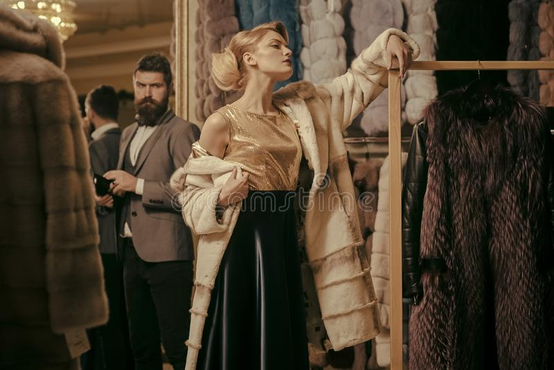 Couple in love tries expensive mink overcoats on. Rich fashion concept. Man and girl with seductive faces at clothes rack background. Guy with beard and women stock photo