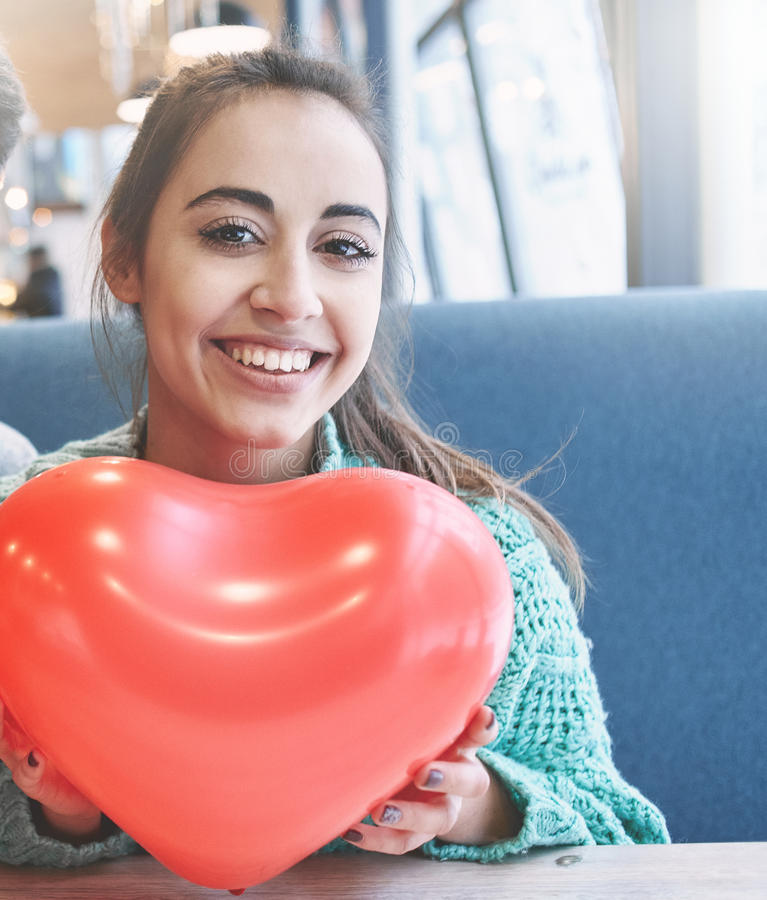 Couple in love in Valentines day. Woman with balloon in the form of heart in a cafe. Couple in love on a date. Love story and Valentines Day concept royalty free stock photo