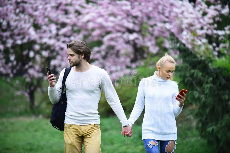 Couple in love walk in spring park. Man and women use mobile phones on blossoming background. Modern life, new technology. Spring, nature awakening, romance royalty free stock photos