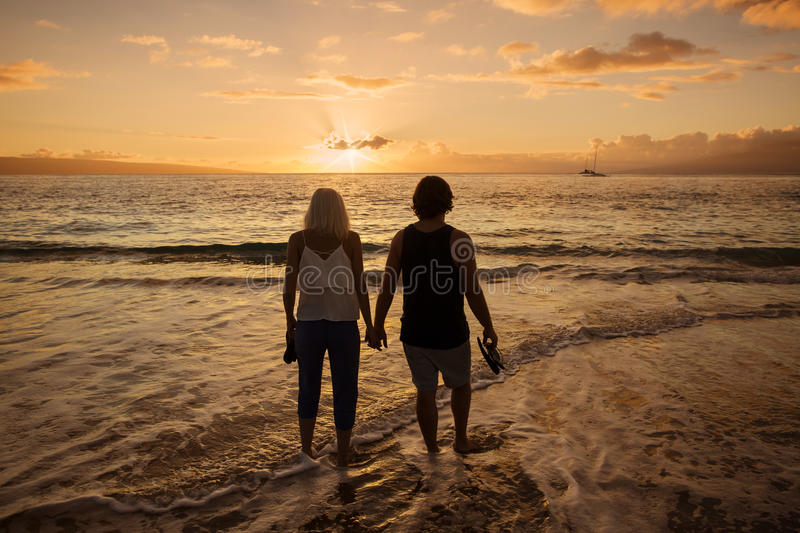 Couple in love walking along the beach together at sunset stock images