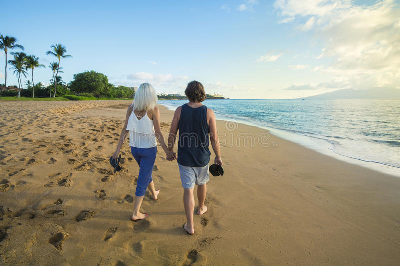 Couple in love walking along the beach together stock images