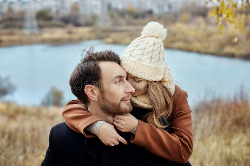 Couple in love walking in the autumn Park, cool fall weather. A man and a woman embrace and kiss, love and affection yellow autumn royalty free stock photos