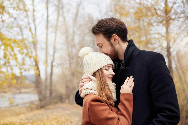 Couple in love walking in the Park, Valentine`s day. A man and a woman embrace and kiss, a couple in love, tender feelings royalty free stock photography