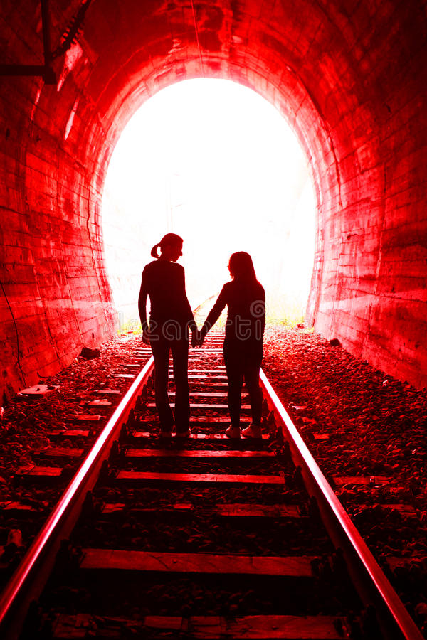 Couple in love walking together through a railway tunnel stock photos