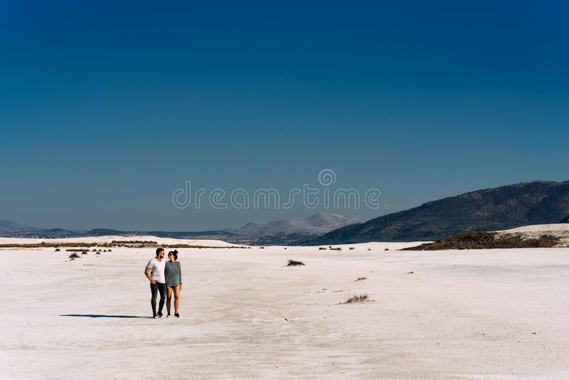 A couple in love walks through the desert royalty free stock images