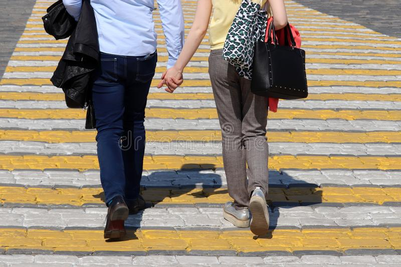 Couple in love walks on pedestrian crossing holding hands royalty free stock photography