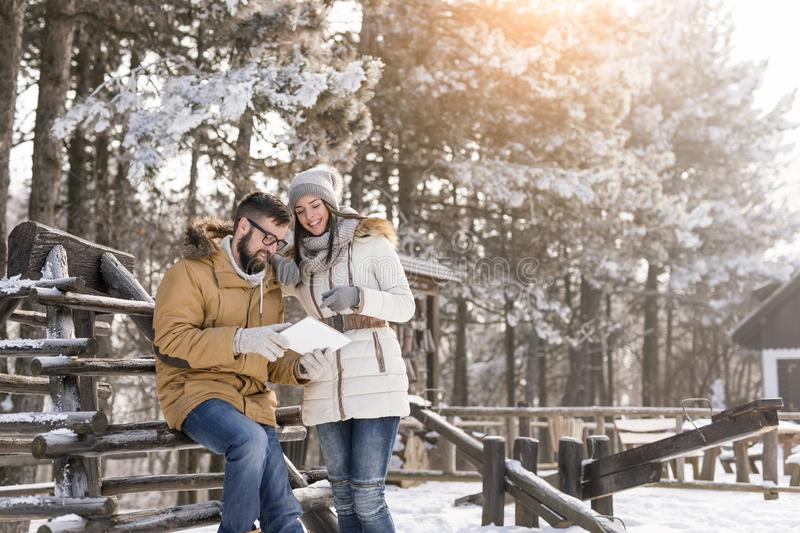 Couple looking at photos taken with tablet computer. Couple in love on a winter vacation looking at photos taken with their tablet computer outdoors on a sunny royalty free stock images