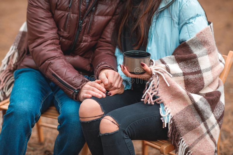 Couple in love, wrapped in a blanket, sit in a cold autumn forest, drink tea and enjoy each other. stock photography