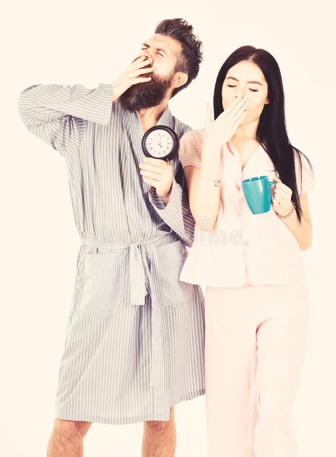 Couple in love, young family in pajama, bathrobe stand isolated on white background. Girl with coffee cup, man hold. Couple in love, young family in pajama stock photos