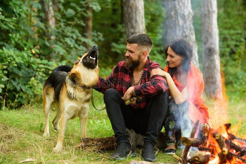 Couple in love, young happy family spend leisure with dog. Family leisure concept. Couple play with german shepherd dog near bonfire, forest background. Woman stock image