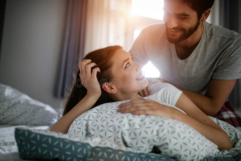 Couple and lovely moments in the bed. Boyfriend giving massage for his beautiful girlfriend stock image