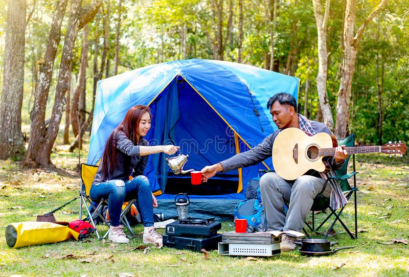 Couple of lover are camping near the forest have relaxing activity with man play guitar and woman give him with a cup of coffee royalty free stock images