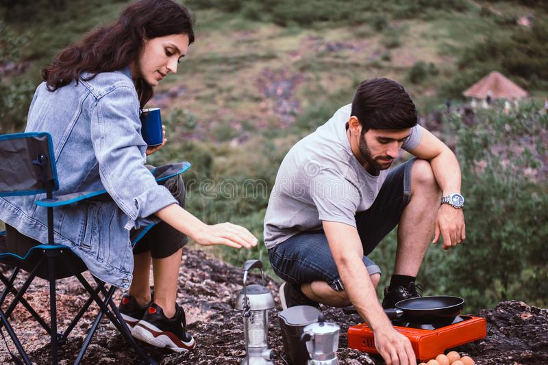 Couple lover cooking food for dinner outside tent together,Enjoying camping concept stock image