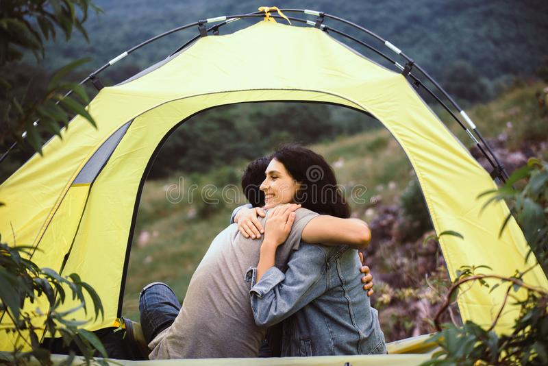 Couple lover hugging together sitting in tent feeling happy and smiling,Enjoying camping royalty free stock images